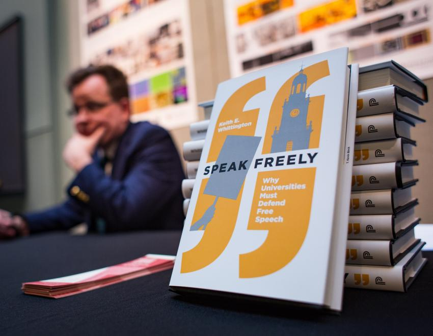 "Professor Whitting at a table with his book ""Speak Freely"""