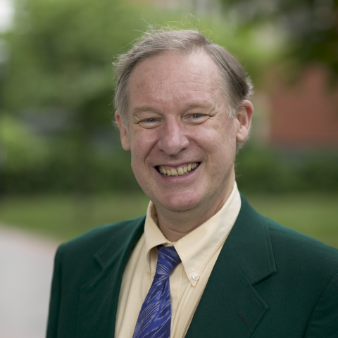 Professor White standing outside smiling in a green blazer and purple tie